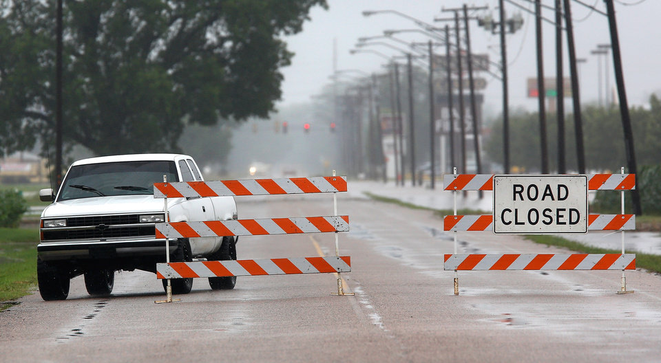 Photo - The city placed these signs on Hardesty Road, east of US 177, after rain from Hurricane Bill produced localized flooding in areas of Pottawatomie County on Thursday, June 18,  2015.   Hardesty Road and US 177. Photo by Jim Beckel, The Oklahoman.