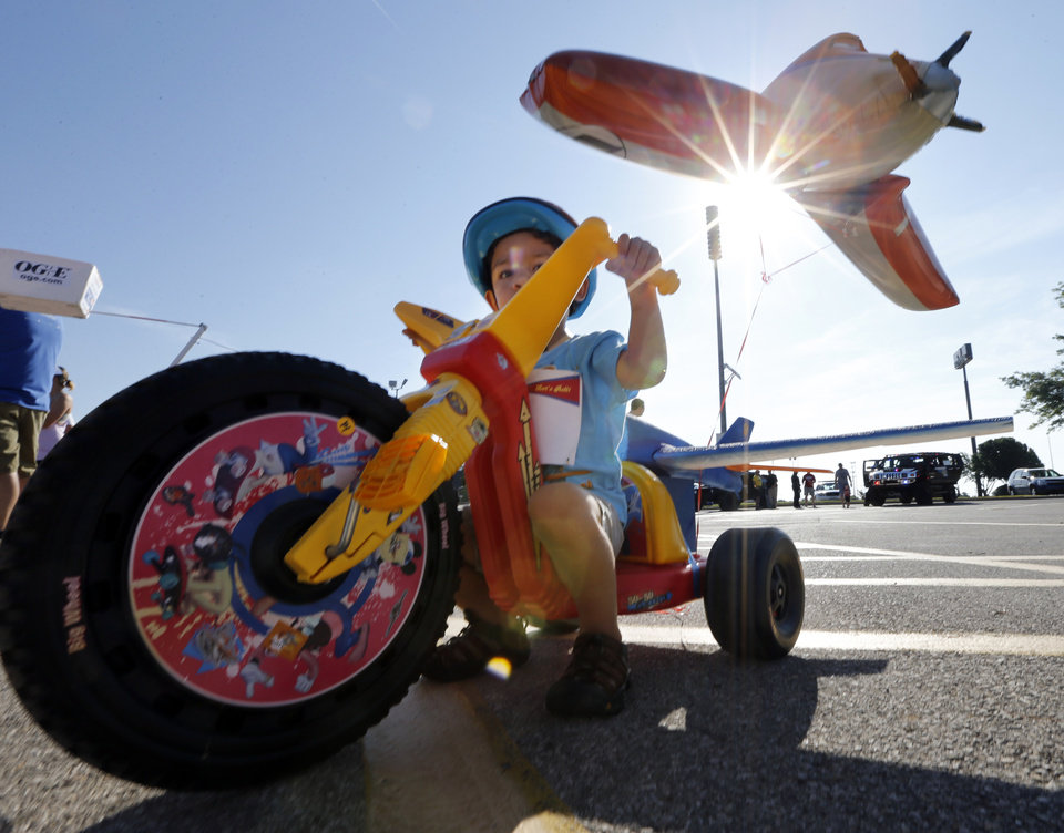 Photo -  Isaac Ozeraglu, 3, pulls a balloon behind his Big Wheel tricycle Saturday as he participates in The Ride, a race in Norman benefiting United Way. PHOTO BY STEVE SISNEY, THE OKLAHOMAN   STEVE SISNEY -
