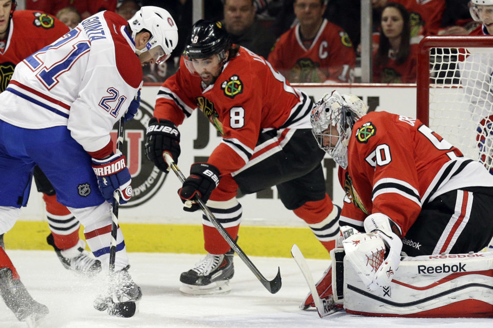 Photo - Montreal Canadiens' Brian Gionta (21) shoots against Chicago Blackhawks goalies Corey Crawford (50) during the first period of an NHL hockey game in Chicago, Wednesday, April 9, 2014. (AP Photo/Nam Y. Huh)