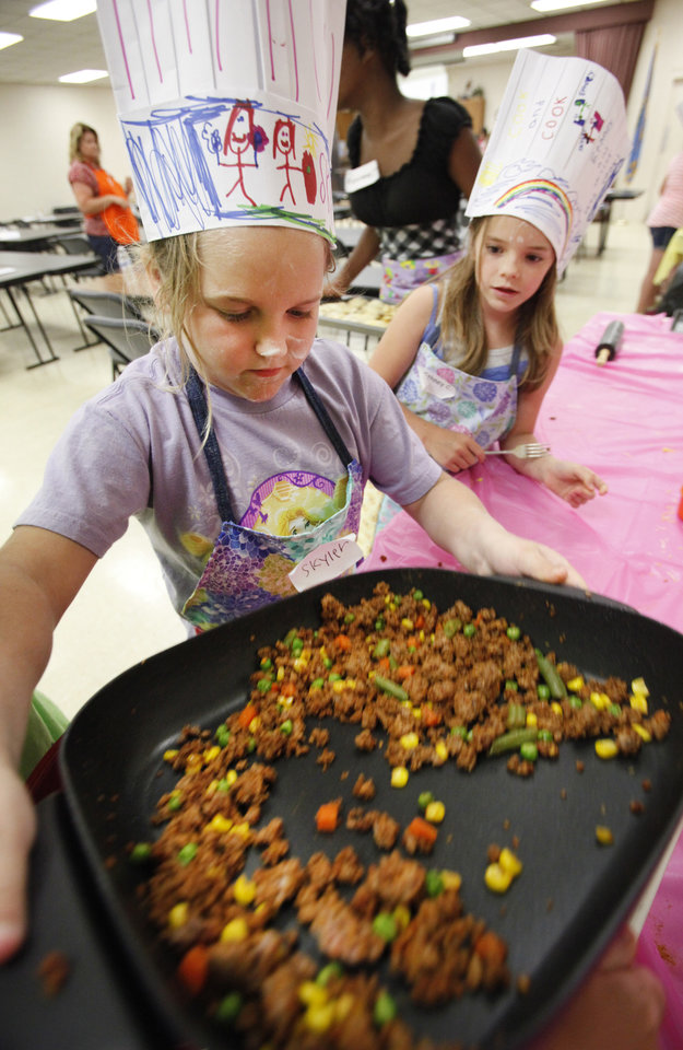 """Photo -  Skyler Williams, 8, and Ethney Clark, 9, work on meat for tacos during the """"Kids in the Kitchen"""" workshop. Photo by David McDaniel, The Oklahoman   David McDaniel -"""