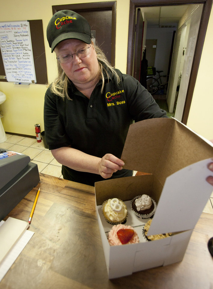 Photo -   In this Wednesday, Aug. 1, 2012 photo, Eve Dobbins boxes up cupcakes at Cupcake Cache, a store run by she and her husband Michael, in Tampa, Fla. They opened Cupcake Cache in April. Money is so tight for the couple that he sold his golf clubs. Eve Dobbins recently took a college teaching job to supplement their income from the business, but both are convinced that with leases so cheap, they made the right move. (AP Photo/John Raoux)