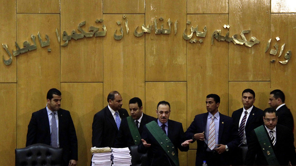 Photo - Presiding Judge Sobhi Abdel-Maguid, center, of the Port Said Criminal Court, holding a hearing in Cairo for security reasons, rules in the case of last year's soccer violence in Port Said which left over 70 dead in Cairo, Egypt, Saturday, March 9, 2013. An Egyptian court has confirmed death sentences handed down against 21 people for their role in a deadly 2012 soccer riot that killed more than 70 people in the city of Port Said. (AP Photo/Ahmed Abd El Latef, El Shorouk Newspaper) EGYPT OUT