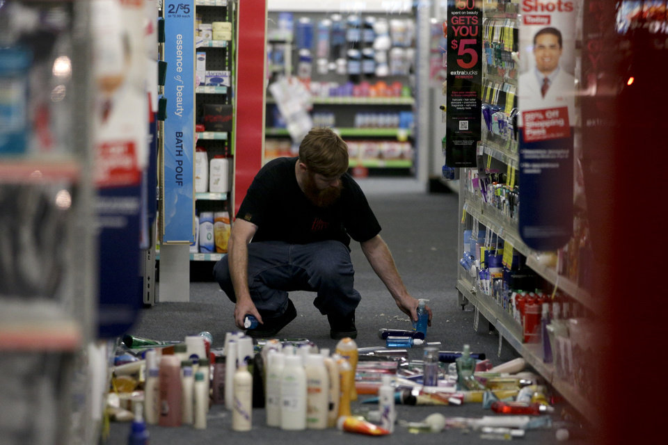 Photo - A man picks up fallen goods at a CVS store after an earthquake on Friday, March 28, 2014, in La Mirada, Calif. A magnitude-5.1 earthquake was widely felt in the Los Angeles area and surrounding counties Friday evening, but authorities said there were no immediate reports of significant damages or injuries. (AP Photo/Jae C. Hong)