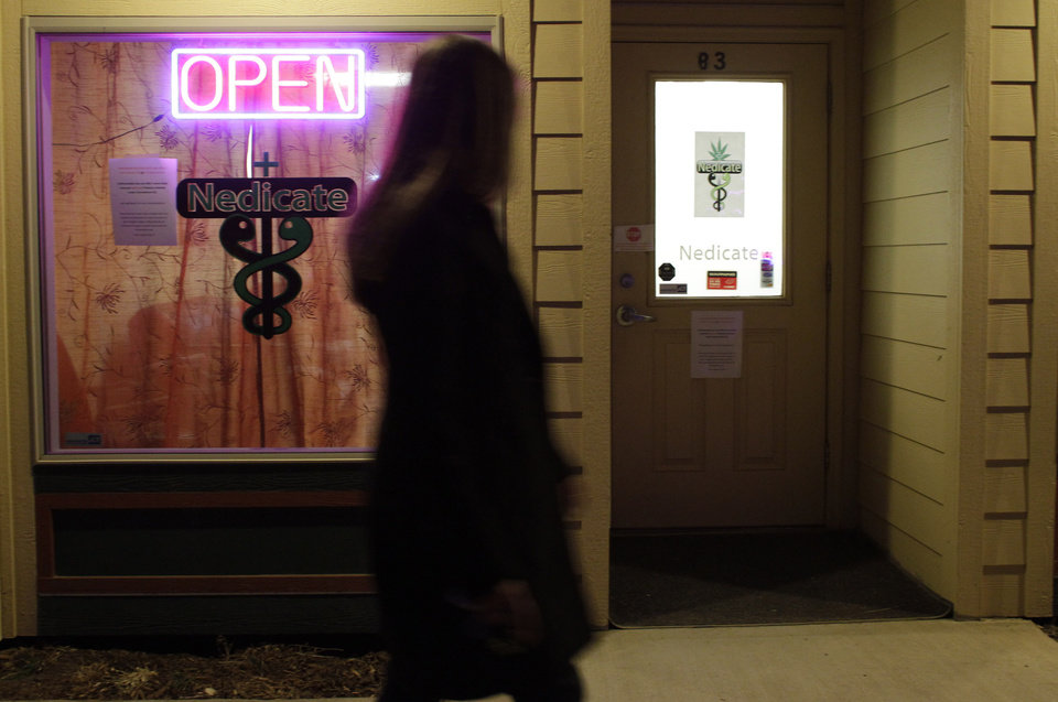 Photo - In this Nov. 19, 2012 photo, a woman walks past a medical marijuana dispensary in the small Rocky Mountain town of Nederland, Colo. On Nov. 6, 2012, Colorado and Washington state legalized the recreational use of marijuana. In Colorado it is set to take effect by Jan. 5, 2013. (AP Photo/Brennan Linsley)