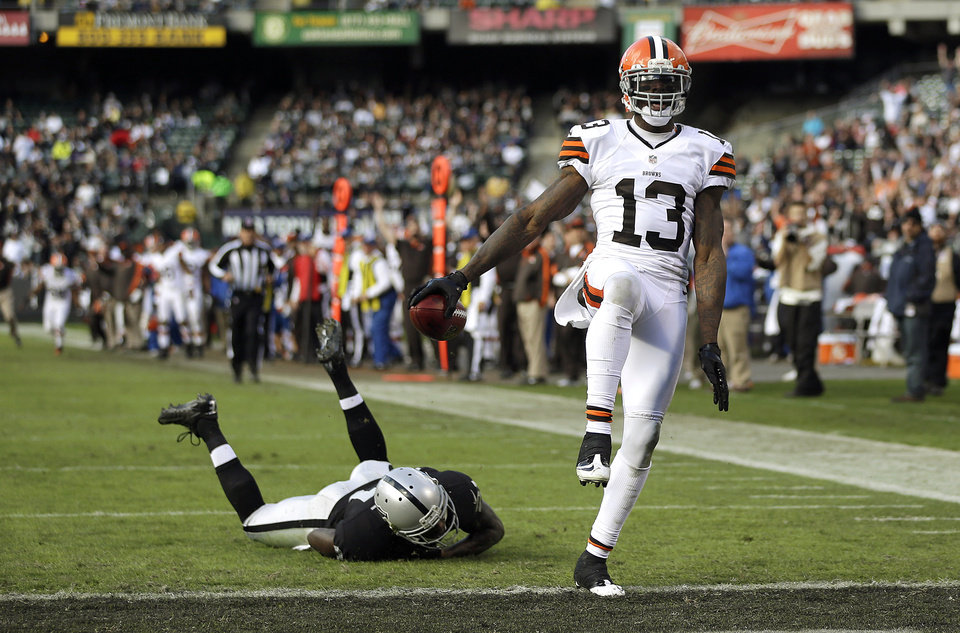 Photo - Cleveland Browns wide receiver Josh Gordon (13) scores on a 44-yard touchdown reception in front of Oakland Raiders defensive back Ron Bartell (21) during the second quarter of an NFL football game, Sunday, Dec. 2, 2012, in Oakland, Calif. (AP Photo/Marcio Jose Sanchez)