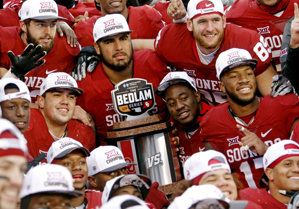 Photo - Players display the Bedlam trophy following the Bedlam college football game between the Oklahoma Sooners (OU) and the Oklahoma State Cowboys (OSU) at Gaylord Family - Oklahoma Memorial Stadium in Norman, Okla., Saturday, Dec. 3, 2016. Photo by Steve Sisney, The Oklahoman