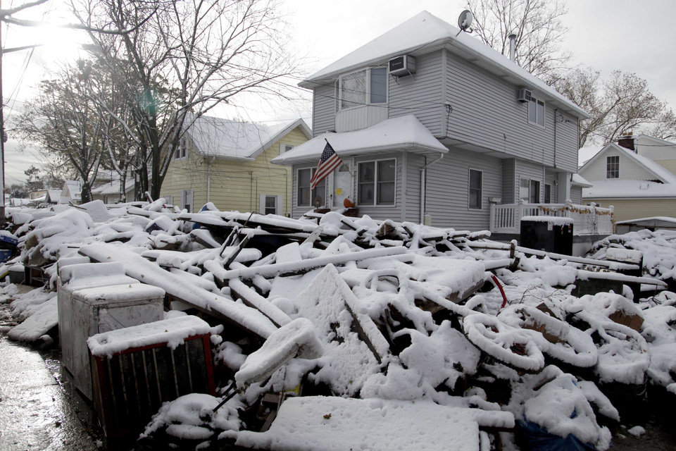 Photo -   A pile of garbage in the street is covered with snow in the New Dorp section of Staten Island, N.Y., Thursday, Nov. 8, 2012. The New York-New Jersey region woke up to a layer of wet snow and more power outages after a new storm pushed back efforts to recover from Superstorm Sandy. (AP Photo/Seth Wenig)
