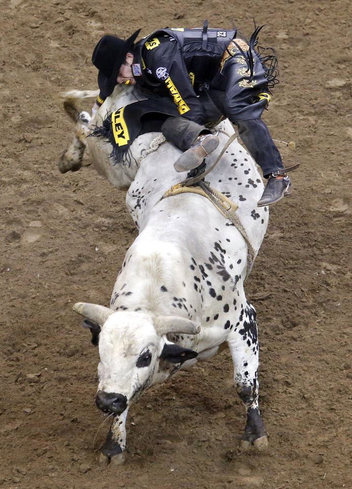 Dougls Duncan rides Johnny Walker Black, Jr. during the WinStar World Casino Invitational PBR bull riding event at Chesapeake Energy Arena in Oklahoma City,  Sunday, Jan. 27, 2013.Photo by Sarah Phipps, The Oklahoman