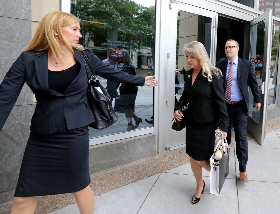 Photo - Maureen McDonnell, center, and two of her lawyers, Heather Martin, left, and Stephen Michael Hauss, right, leave the federal courthouse in Richmond, Va.,Tuesday, July 29, 2014. The corruption trial for ex-Virginia Gov. Bob McDonnell and his wife plunged Tuesday into the sordid details of the couple's marriage and the former first lady's