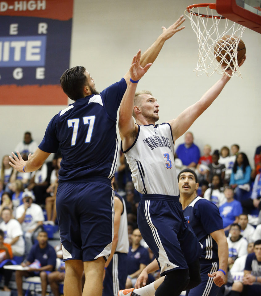 Photo - Oklahoma CIty's Domantas Sabonis goes past Joffrey Lauvergne during the Thunder's annual Blue and White Scrimmage at John Marshall Mid-High School in Oklahoma City, Tuesday, Sept. 27, 2016. Photo by Bryan Terry, The Oklahoman