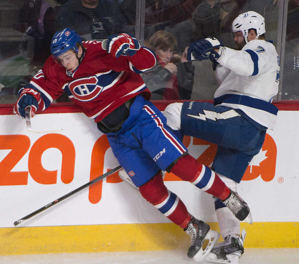 Photo - Montreal Canadiens Nathan Beaulieu and Tampa Bay Lightning Radko Gudas collide as they scramble for the puck during first period of an NHL game in Montreal Saturday, Feb. 1, 2014. (AP Photo/The Canadian Press, Peter McCabe)