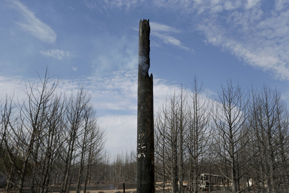 A burned utility pole smolders around burned trees, Sunday, Aug. 5, 2012, in Glencoe, Okla., after wildfires moved through the area Saturday. Photo by Sarah Phipps, The Oklahoman