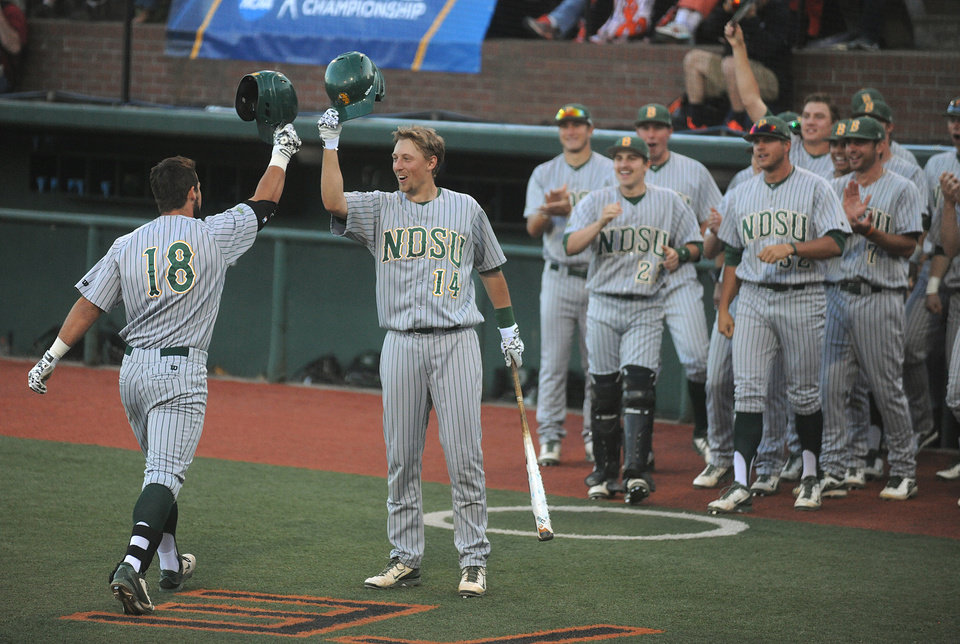 Photo - North Dakota State's Kyle Kleinendorst (18) celebrates with teammate Michael Leach (14) after a solo home run against Oregon State during an NCAA college baseball tournament regional  game in Corvallis, Ore., Friday, May 30, 2014. (AP Photo/Mark Ylen)