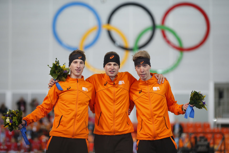 Photo - Speedskaters from the Netherlands, from right to left, bronze winner Jorrit Bergsma, gold winner Sven Kramer and silver winner Jan Blokhuijsen stand together during the flower ceremony for the men's 5,000-meter speedskating race at the Adler Arena Skating Center during the 2014 Winter Olympics, Saturday, Feb. 8, 2014, in Sochi, Russia. (AP Photo/Pavel Golovkin)
