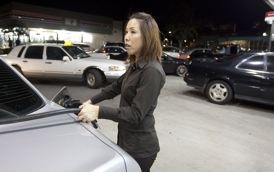 Photo - Lisa Matsuda of Manoa fills her car with gas along with other Oahu residents due to a tsunami warning Thursday, March 10, 2011. A large 8.9 earthquake of Japan is believed to have generated a tsumani wave. The Pacific Tsunami Center expects the wave to hit Hawaii at 2:59 a.m. Hawaiian Standard Time. (AP Photo/Eugene Tanner) ORG XMIT: HIET101