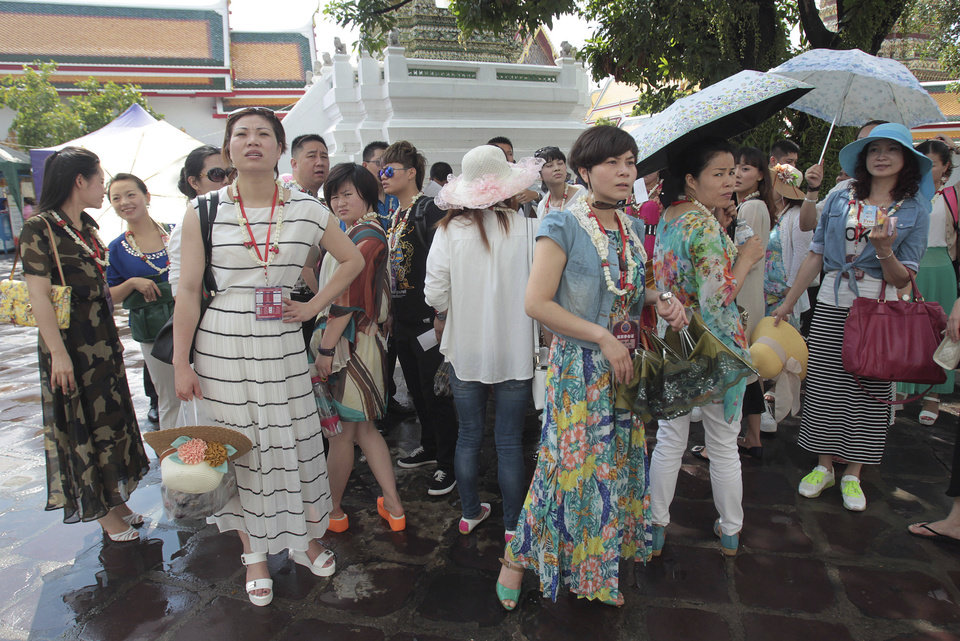 Photo - A group of Chinese tourists take a shelter in the shade while touring Wat Pho in Bangkok, Thailand Tuesday, May 27, 2014. The drama of Thailand's military takeover has played out mainly in the political arena. While the army detains political leaders and issues stern warnings on TV, tourists are kicking back on the country's famed beaches and sightseeing in Bangkok. The main impact on visitors for now is a 10 p.m. curfew, which forces nightlife to close four hours earlier. (AP Photo/Sakchai Lalit)