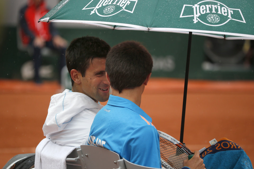 Photo - Serbia's Novak Djokovic, left, talks to a ball boy after inviting him to sit on his bench during a break during the first round match of the French Open tennis tournament against Portugal's Joao Sousa at the Roland Garros stadium, in Paris, France, Monday, May 26, 2014. (AP Photo/Michel Euler)