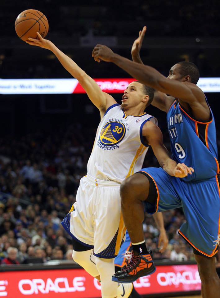 The Golden State Warriors' Stephen Curry (30) goes to the hoop past the Oklahoma City Thunder's Serge Ibaka (9) at Oracle Arena in Oakland, California, on Wednesday, January 23, 2013. (Jane Tyska/Oakland Tribune/MCT)