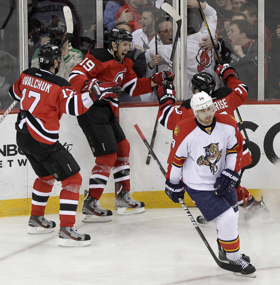 Photo -   Florida Panthers' Tomas Fleischmann, bottom right, of the Czech Republic, skates away as New Jersey Devils' Travis Zajac (19) celebrates with teammates Ilya Kovalchuk, left, of Russia, and Zach Parise, right, after scoring the game-winning goal during the overtime of Game 6 of a first-round NHL hockey Stanley Cup playoff series, Tuesday, April 24, 2012, in Newark, N.J. The Devils won 3-2, forcing a seventh game. (AP Photo/Julio Cortez)