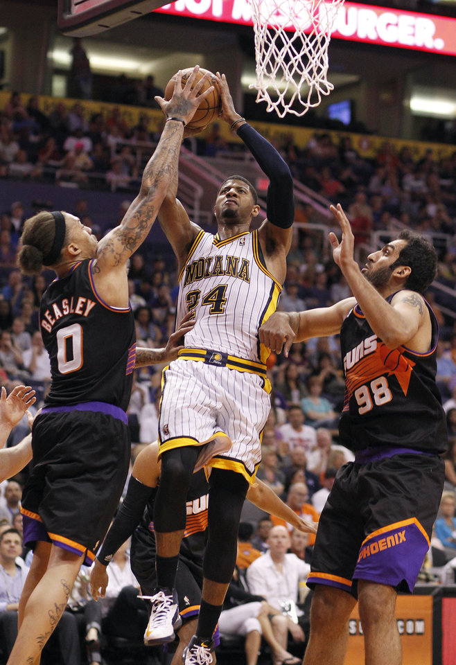 Indiana Pacers forward Paul George, center, attempts a field goal between Phoenix Suns forward Michael Beasley, left, and Hamed Haddadi, right, of Iran, during the first half of an NBA basketball game, Saturday, March 30, 21013, in Phoenix. (AP Photo/Paul Connors)