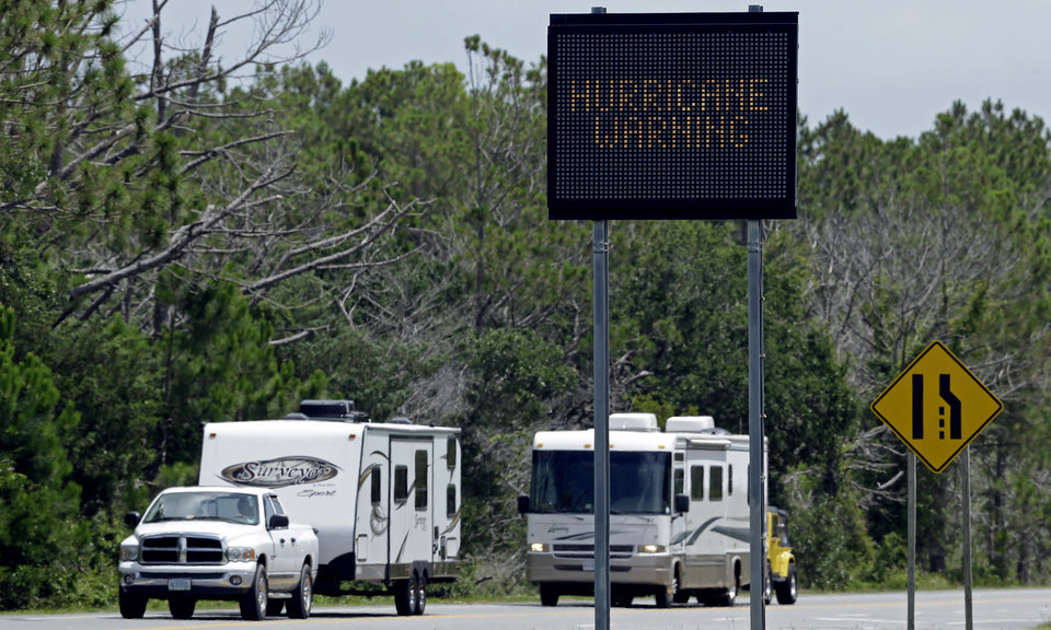 Photo - A sign warns travelers as recreational vehicles arrive in Nags Head, N.C., after departing Hatteras Island Thursday, July 3, 2014. Hurricane Arthur is forecast to pass by Hatteras Friday morning.  The island is under mandatory evacuation orders. (AP Photo/Gerry Broome)