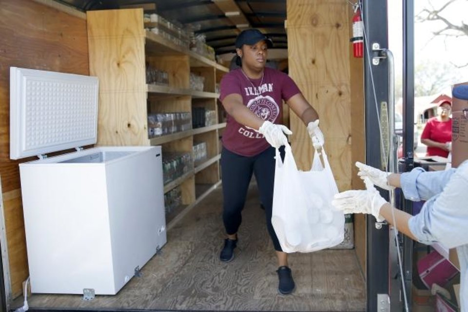 Photo - Mauri Hubbard helps bag food at a drive-thru food distribution for Oklahoma City school students outside The Market at Restore OKC in Oklahoma City, Thursday, March 26, 2020. The drive-thru food distribution was set up on site by Skyline Urban Ministry. [Bryan Terry/The Oklahoman]