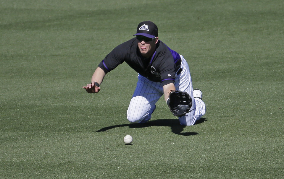 Photo - Colorado Rockies center fielder Corey Dickerson can't get a glove on a base hit by Oakland Athletics' Addison Russell during the sixth inning of a spring training baseball game in Scottsdale, Ariz., Saturday, March 8, 2014. (AP Photo/Chris Carlson)