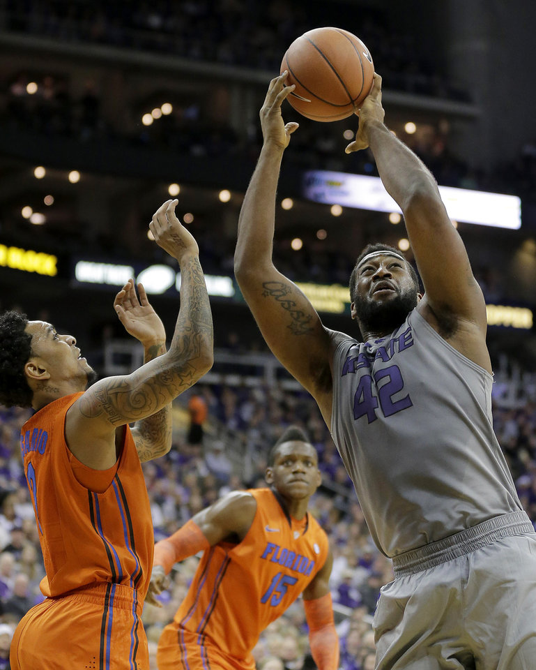 Kansas State forward Thomas Gipson (42) beats Florida guard Mike Rosario, left, to a rebound during the first half of an NCAA college basketball game on Saturday, Dec. 22, 2012, at the Sprint Center in Kansas City, Mo. (AP Photo/Charlie Riedel)