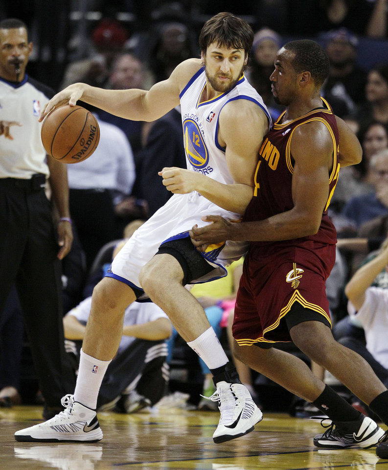 FILE - In this Nov. 7, 2012, file photo, Golden State Warriors center Andrew Bogut (12), of Australia, backs down against Cleveland Cavaliers power forward Samardo Samuels (24) during the first half of an NBA basketball game in Oakland, Calif. Bogut insists he will no longer even attempt to guess when he will return to the court for the Warriors, saying he is out