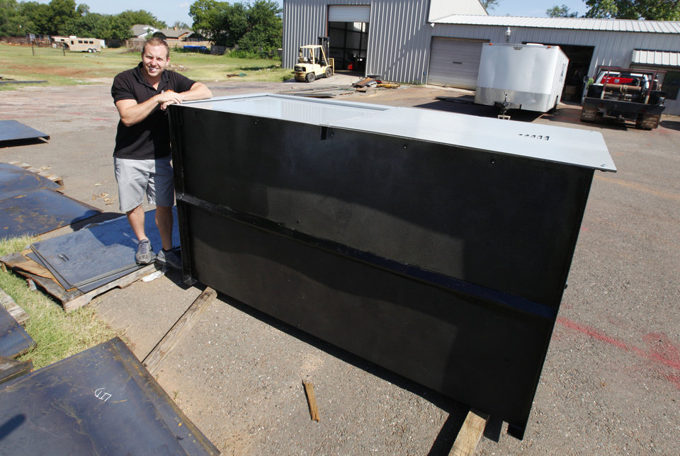 Photo - Corey Churchill, owner of Weather Tech, with a storm shelter he manufactures in Oklahoma City Thursday, July 28, 2013. The shelters are designed to be installed in garage floors.  Photo by Paul B. Southerland, The Oklahoman