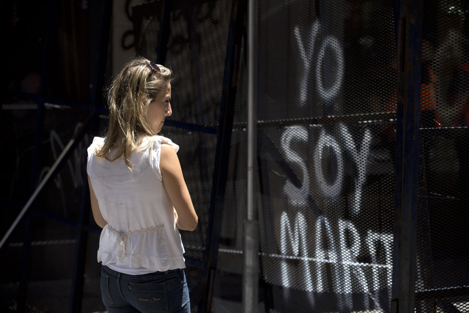 Photo - A woman looks at graffiti that reads in Spanish