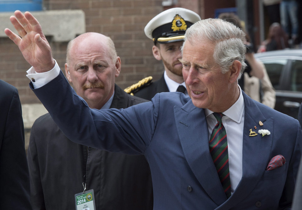 Photo - Prince Charles waves to the crowd while crossing a street Wednesday, May 21, 2014 in Winnipeg. The Royal couple are on a four-day tour of Canada. (AP Photo/The Canadian Press, Paul Chiasson)