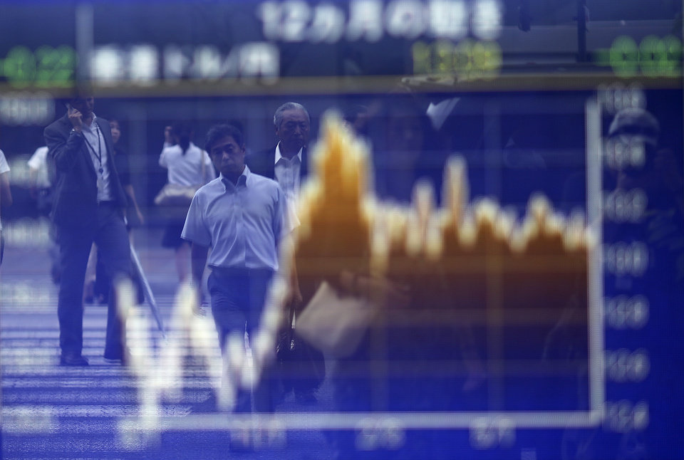 Photo - Pedestrians are reflected on an electronic stock board of a securities firm in Tokyo, Thursday, July 17, 2014. Asia's major stock markets mostly posted modest gains Thursday after positive U.S. corporate and economic news underpinned confidence. (AP Photo/Eugene Hoshiko)