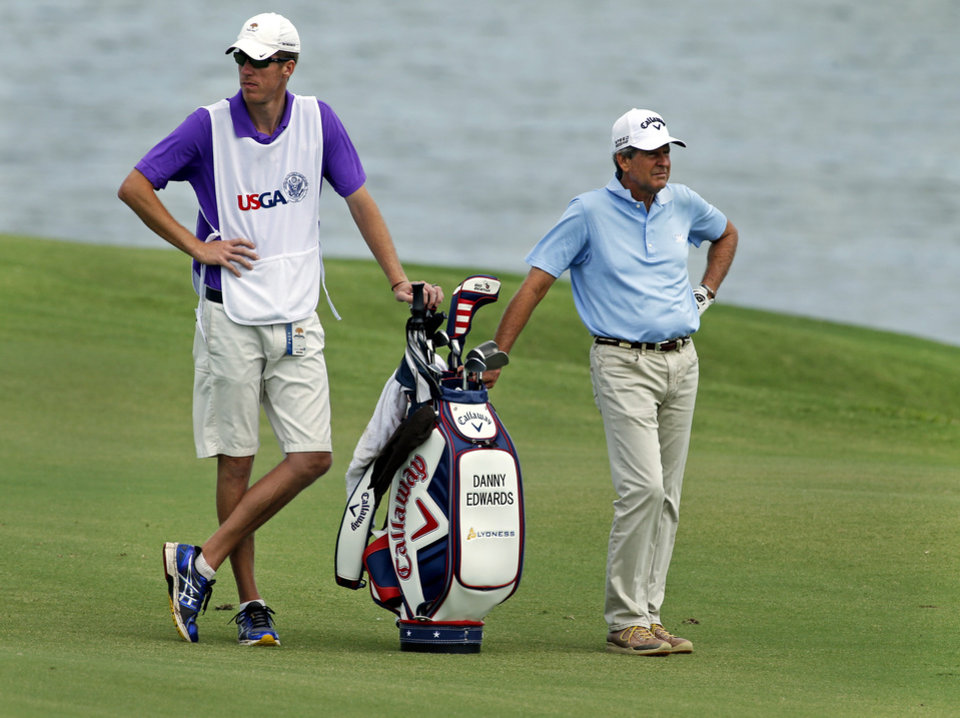 Photo - Danny Edwards waits with his caddy for a second shot on hole 11 during the first round of the U.S. Senior Open Championship golf tournament at Oak Tree National in Edmond, Okla. on Thursday, July 10, 2014. Photo by Steve Sisney, The Oklahoman