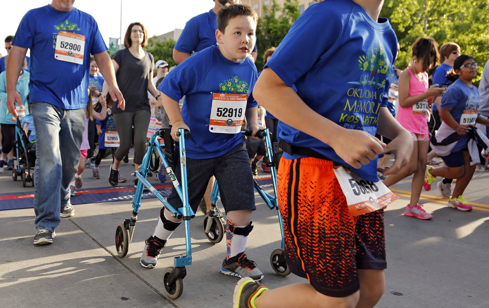 Photo -  Luke Stafford, 8, uses his walker Sunday as he takes part in the kids marathon during the Oklahoma City Memorial Marathon. Stafford suffers from cerebral palsy, and this is his second year to finish the 1.2-mile kids marathon. [Photo by Chris Landsberger, The Oklahoman]