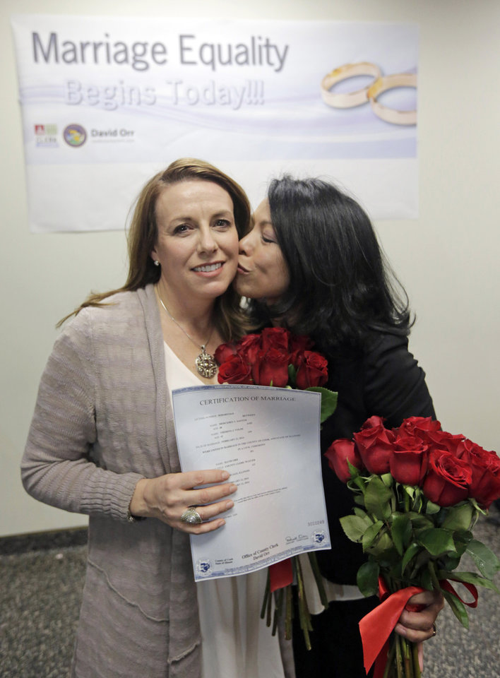 Photo - Theresa Volpe, left, and Mercedes Santos show off their Certification of Marriage after being married by Cook County Clerk David Orr, Friday, Feb. 21, 2014, in Chicago. Judge Sharon Johnson Coleman's Friday order says there is no reason to delay same-sex marriages in Illinois until June, when the state's law is set to take effect. Her finding applies only to Cook County, where Chicago is located. (AP Photo/M. Spencer Green)