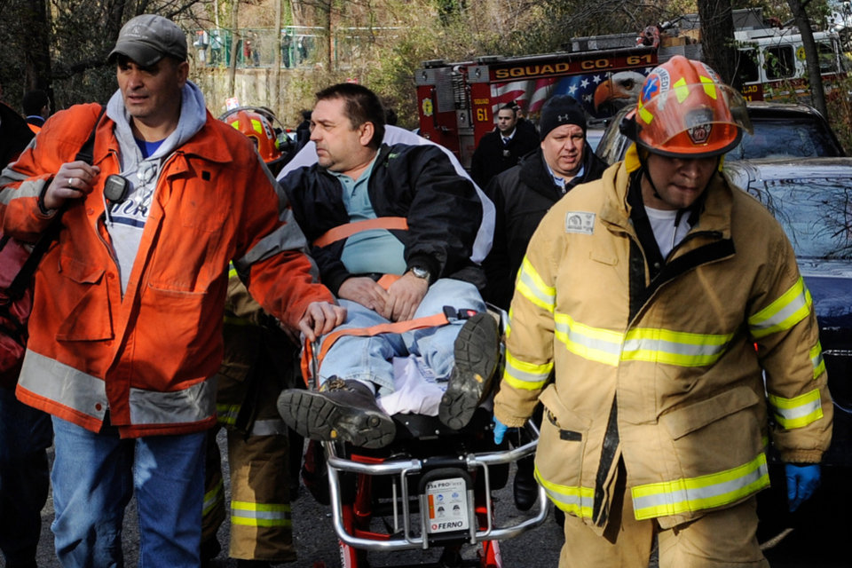 Photo - FILE - In this Dec. 1, 2013 photo, Metro-North Railroad engineer William Rockefeller is wheeled on a stretcher away from the area where the commuter train he was operating derailed in the Bronx borough of New York. According to a Federal Railroad Administration review prompted by the derailment that killed four passengers and injured about 70 others, the Metro-North commuter railroad has allowed its emphasis on trains' on-time performance to