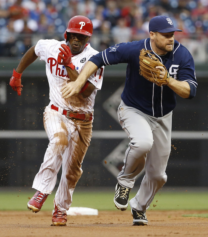 Photo - Philadelphia Phillies' Jimmy Rollins, left, brushes past San Diego Padres third baseman Chase Headley to steal to third during the first inning of a baseball game on Wednesday, June 11, 2014, in Philadelphia. Rollins stole second and third base on the same play after the Padres left third uncovered while playing a defensive shift for hitter Ryan Howard. (AP Photo/Matt Slocum)