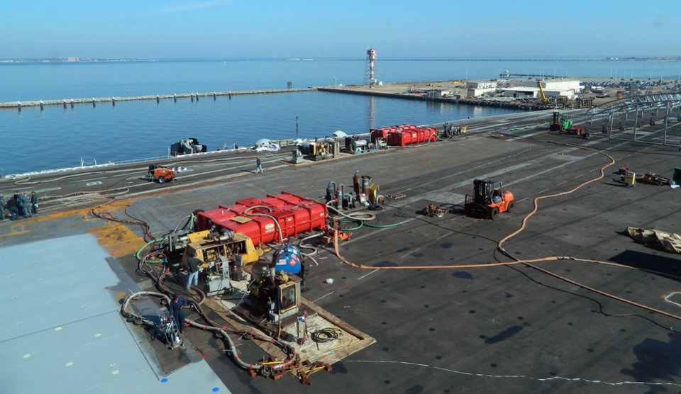 Photo - The deck of the aircraft carrier the USS Dwight D. Eisenhower is resurfaced as it is docked in Norfolk, Va., for repairs and maintenance, on Jan. 29, 2013. U.S. officials say that budget strains will force the Pentagon to cut its aircraft carrier presence in the Persian Gulf area from two carriers to one. The Eisenhower was in the Gulf but was brought home in December for maintenance. It will return later this month, but plans for the USS Harry S. Truman to deploy to the Gulf this week have been canceled. (AP Photo/Lolita Baldor)