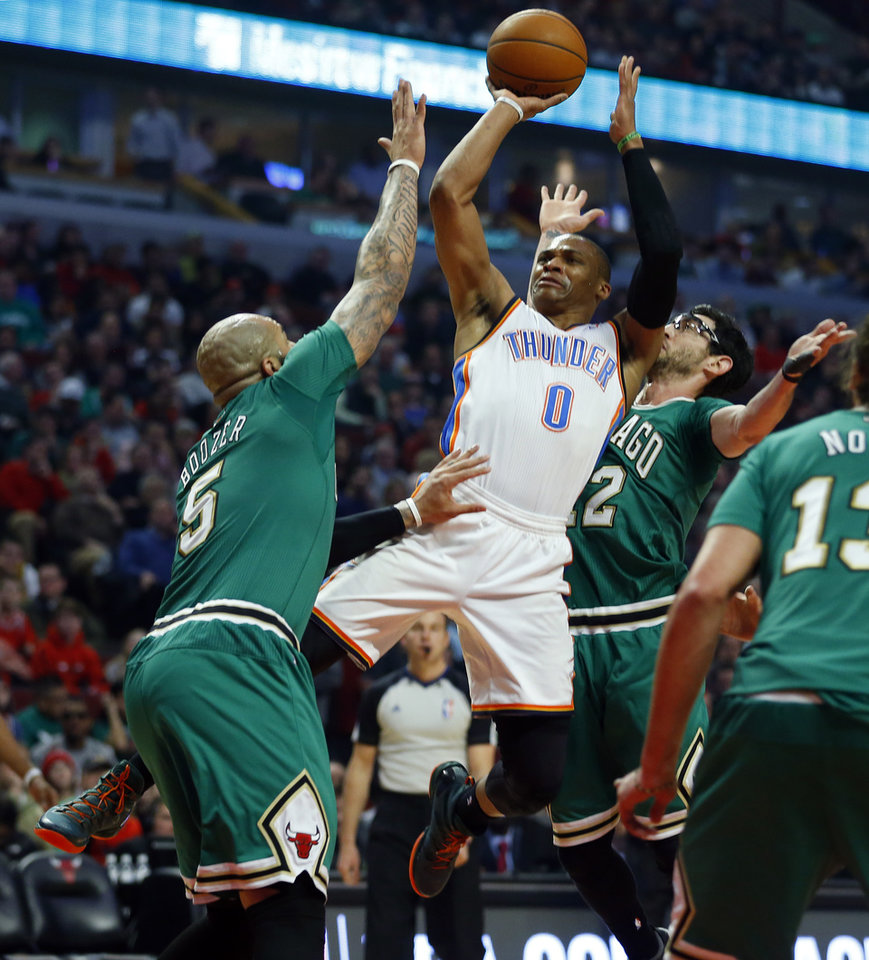 Photo - Oklahoma City Thunder guard Russell Westbrook (0) shoots over Chicago Bulls forward Carlos Boozer (5) and Kirk Hinrich, right, during the first half of an NBA basketball Monday, March 17, 2014, in Chicago.  (AP Photo/Jeff Haynes)