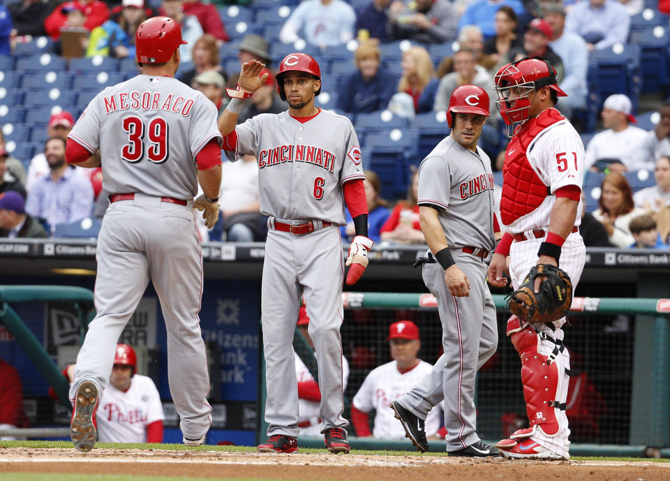 Photo - Cincinnati Reds' Devin Mesoraco, left, comes home after hitting a three-run home run scoring, Billy Hamilton, center left, and Skip Schumaker, center right, as Philadelphia Phillies' Carlos Ruiz, right, watches during the first inning of a baseball game, Friday, May 16, 2014, in Philadelphia. (AP Photo/Chris Szagola)