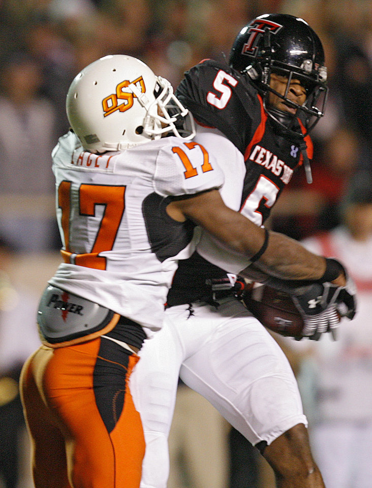 Photo - Texas Tech's Michael Crabtree (5) pulls in a pass in front of Oklahoma State's Jacob Lacey (17) during the first half of the college football game between the Oklahoma State University Cowboys (OSU) and the Texas Tech Red Raiders at Jones AT&T Stadium on Saturday, Nov. 8, 2008, in Lubbock, Tex.BY CHRIS LANDSBERGER/THE OKLAHOMAN