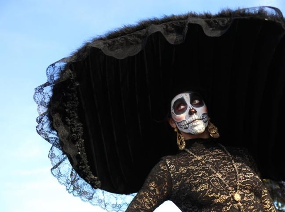 Photo -  A broad, black hat frames the face of Eden Cook, 20, during the Day of the Dead Festival Sunday in the Plaza District. [DOUG HOKE/THE OKLAHOMAN]