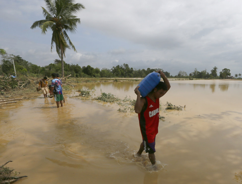 Photo - Residents walk back to their homes with drinking water as they begin cleaning up their homes in Cabanatuan, northern Philippines, Tuesday, Oct. 20, 2015, two days after Typhoon Koppu battered the city and nearby provinces. Slow-moving Typhoon Koppu blew ashore with fierce wind in the northeastern Philippines early Sunday, toppling trees and knocking out power and communications and forcing the evacuation of thousands of villagers. (AP Photo/Bullit Marquez)
