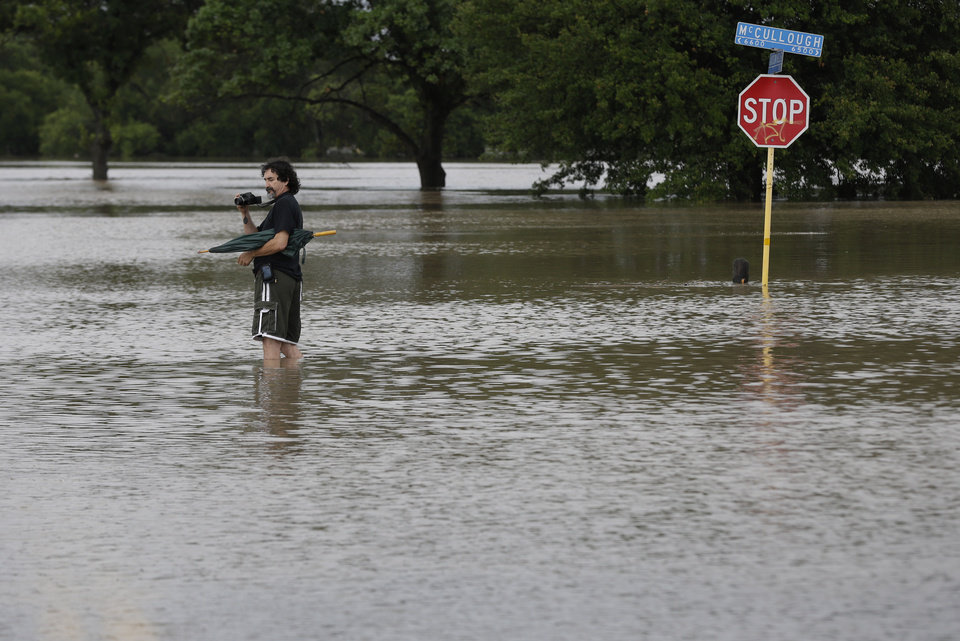 Photo - A man photographs floodwaters caused by heavy rains, Saturday, May 25, 2013, in San Antonio. The city has received torrential rains since Friday evening and officials say numerous roads have been closed because of flash flooding. (AP Photo/Eric Gay)
