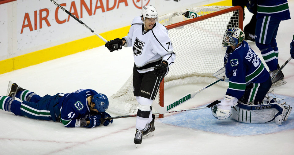 Los Angeles Kings\' Jordan Nolan, center, celebrates after scoring as Vancouver Canucks\' Andrew Alberts, left, lies on the ice and goalie Cory Schneider, right, watches during the second period of an NHL hockey game in Vancouver, British Columbia on Saturday, March 2, 2013. (AP Photo/The Canadian Press, Darryl Dyck)