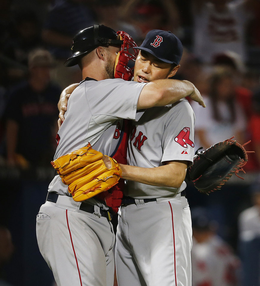Photo - Boston Red Sox catcher David Ross, left, and relief pitcher Koji Uehara (19) celebrate after Boston defeated the Atlanta Braves 6-3 in a baseball game Tuesday, May 27, 2014, in Atlanta. Uehara was credited with a save. (AP Photo/John Bazemore)