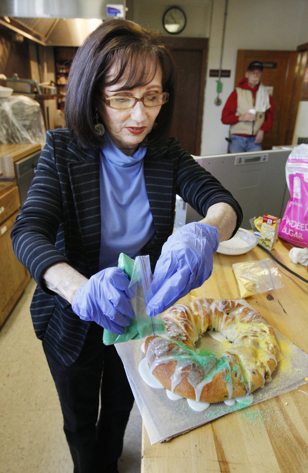 Photo - Volunteer Deena Palmer decorates a king cake baked for a fundraiser at Douglas Boulevard United Methodist Church in Midwest City.  PAUL B. SOUTHERLAND - PAUL B. SOUTHERLAND