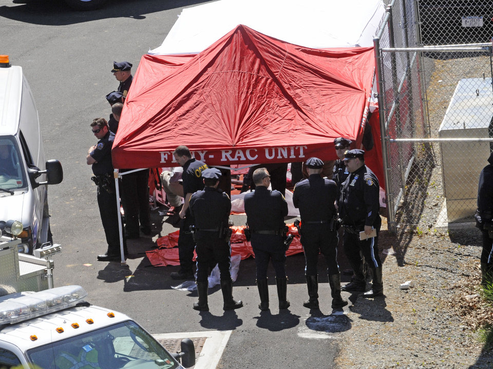 Photo -   Police surround a temporarily built tent where the victims of a vehicle crash were brought, Sunday April 29, 2012, in New York. Authorities say the out-of-control van plunged off a roadway near the Bronx Zoo, killing seven people, including three children. (AP Photo/ Louis Lanzano)