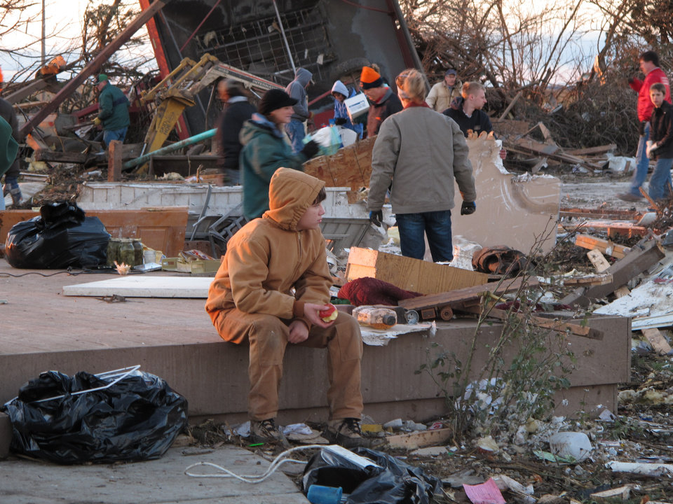 Photo - A young boy takes a break from helping comb the rubble of Curt Zehr's home just outside Washington, Ill., on Sunday, Nov. 17, 2013. Zehr's wife and adult son took shelter in their basement as a tornado destroyed their farm house they were not injured. The tornado cut a path of destruction through Washington. (AP Photo/David Mercer)